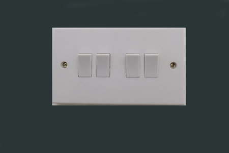 Four way electrical light switch.  White plastic switch with two screws and set against dark grey background.
