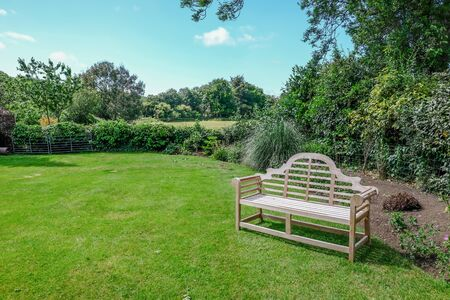Tranquil english country garden with rural view and wooden bench.  Taken on a sunny morning in Sussex.