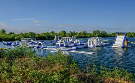 Fairlop, Essex, UK - May 16, 2019: View of the Aqua Bounce floating obstacle course, newly installed on the lake at Fairlop Waters