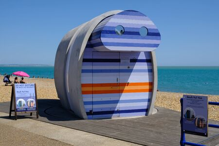 Eastbourne, Sussex, England, UK - August 1, 2018:  Brightly coloured modern beach hut for hire on the front at Eastbournes beach.