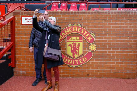 Old Trafford, Manchester, UK - January 20, 2019: Couple of supporters taking a selfie in front of the Home Team dugout at the Manchester United football club stadium.