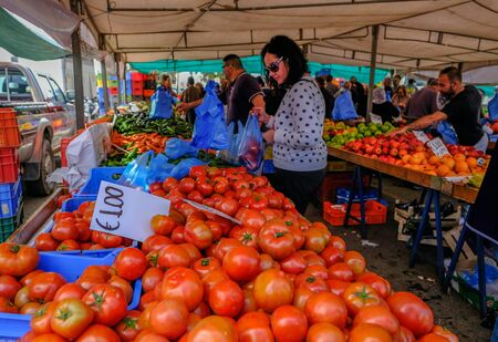 Limassol, Cyprus - March 23, 2019: Vibrant market stall at a farmers market with lots of shoppers choosing and buying their vegetables. Sajtókép
