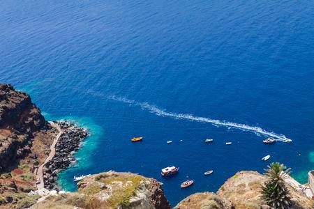Boats in the sea near the coast of Oia village on Santorini island, Greece Stock Photo