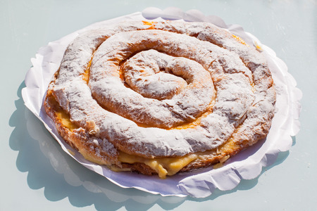 Ensaimada with cream, spiral shaped pastry typical of Majorca, Spain
