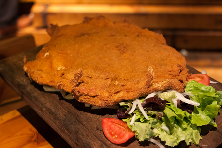 Cachopo, a typical dish of the Asturias region of Spain that consists of two large breaded veal fillets filled with ham and cheese, served on a wooden cutting board Stock Photo