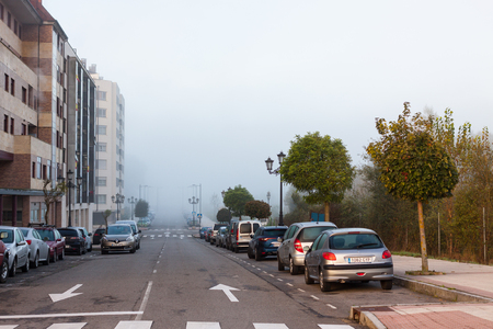OVIEDO, SPAIN - OCTOBER 31, 2017: Cars parked along the road in Oviedo in the early morning with a thick morning fog