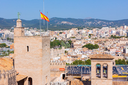 View of the Almudaina Palace with mountains in the background from the terrace of the Cathedral of Santa Maria of Palma, also known as La Seu. Palma, Mallorca, Spain Stock Photo