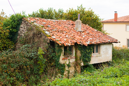 Small rural house covered with green ivy in La Espina, Asturias, Spain
