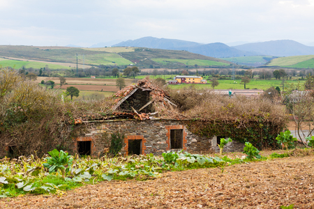 Small rural house with green hills in the background in Asturias, Spain