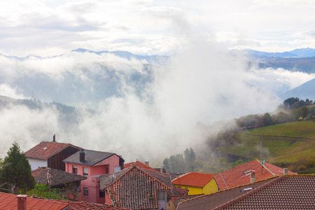 Houses with mountains in the fog in the background in Tineo, Asturias, Spain Stock Photo