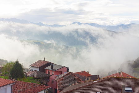 Landscape with some houses and mountains in the fog in Tineo, Asturias, Spain