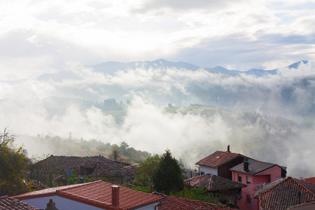 Houses with mountains in the fog in the background in Tineo, Asturias, Spain Stock Photo - 107711328