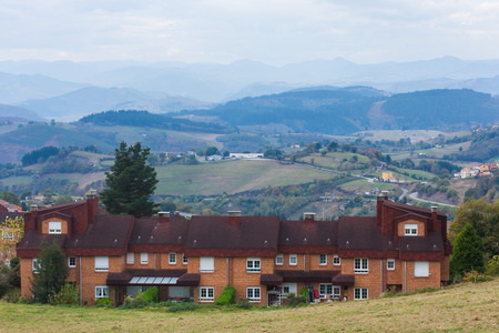 Nice brick house with mountains in the background in Tineo, Asturias, Spain Stock Photo