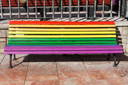 Rainbow bench painted in the colors of LGBT pride flag on Plaza de La Escandalera in Oviedo, Asturias, Spain Stock Photo - 107711265