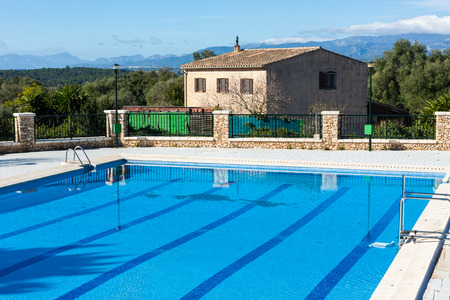 Municipal swimming pool with mountains in the background in Costitx, Mallorca, Spain Stock Photo