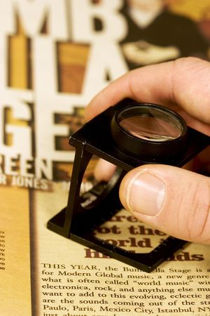 Hand holding a loupe proffing magazine or newspaper print.  up close and personal shot, getting the details right, doing a good job for your company.
