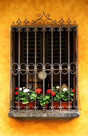 Bright yellow stucco wall with iorn gated window with sill full of red and white geraniums