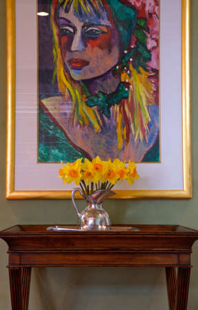 Interior Design Bright Painting with daffodills in a silver vase sitting on a side table photo