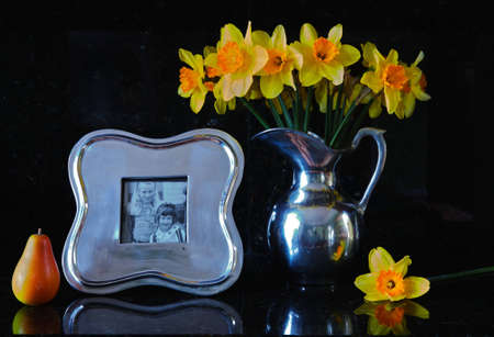 still life of pewter vase and frame with two little girls in it. Daffodills and a pear accent the silver on a dark granite background