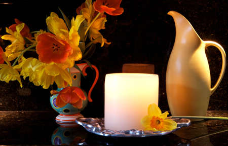 Beautiful pewter vase full of orange and yellow tulips, and a yellow antique pitcher, with a lit, glowing candle all on a black granite background