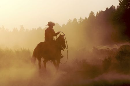 Cowboy outside in the setting sun Stock Photo