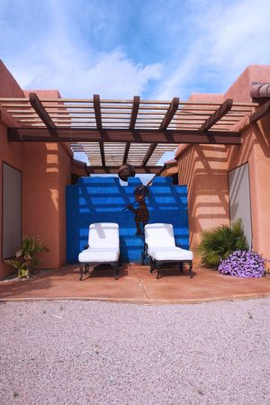 Mexican Veranda with two iorn chairs against a colorful background Stock Photo