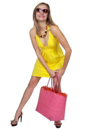 Pretty blond in a bright yellow halter dress with high heels and a pink bag photo
