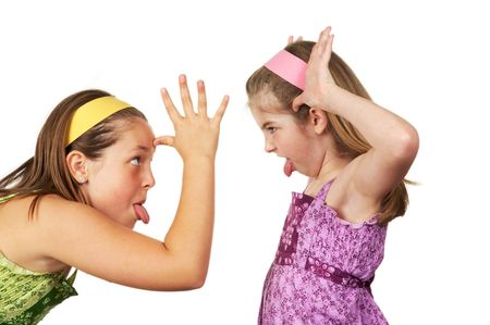 Two young girls fighting and sticking their tongues out at each other Banque d'images