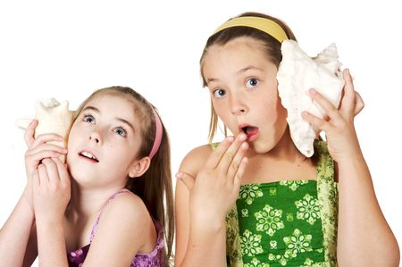 Two young gradeschool girls listening to seashell stories and secrets Stock Photo - 3042880