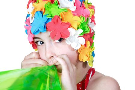 Beautiful little girls in a flowered swim cap blowing up a bright green inner tube Stock Photo