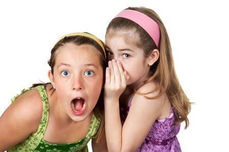Two young gradeschool girls telling secrets