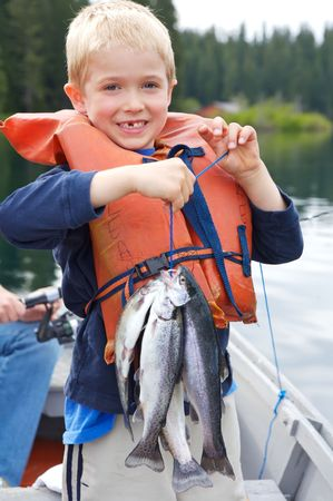 Little boy holding four trout with a big toothless smile on his face