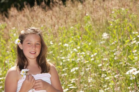 Pretty young and healthy girl standing in a field of daisies photo