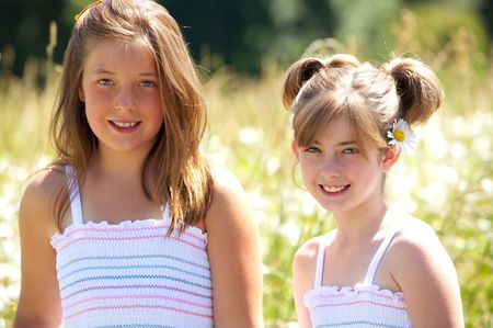 Two cute young girls in matching dresses with big smiles