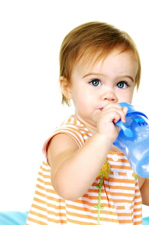 Cute toddler holding a sippy cup drinking water Banque d'images