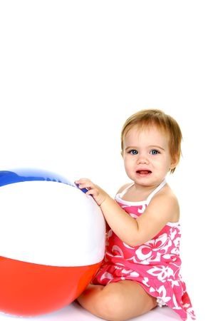 Cute little toddler girl with a big beach ball on white background photo