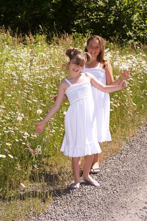 Pretty young girls walking by a field of daisies