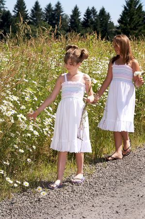 Pretty young girls standing next to a field of daisies photo