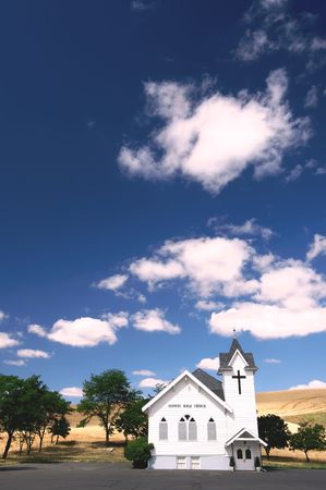 Old white country church with wheat fields and blue sky with puffy clouds