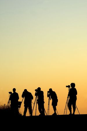 Silouette of five photographers lined up shooting photos Stock Photo