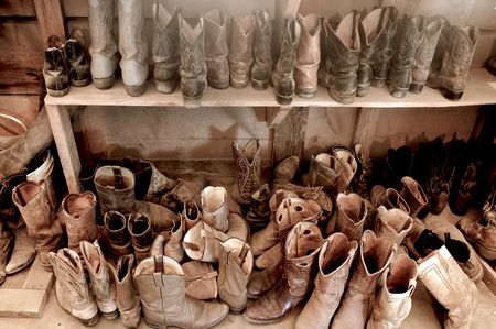 botas vaqueras: Tack sala llena de vaquero y botas desgastadas Foto de archivo