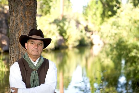 Handsome older cowboy leaning against a tree Stock Photo - 3619551