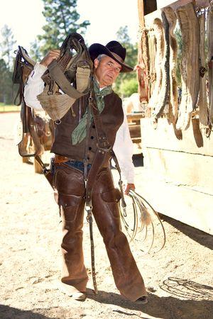 Handsome older cowboy carrying saddle at barn