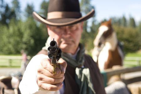 Cowboy aiming gun, focus only on gunpoint, horse in