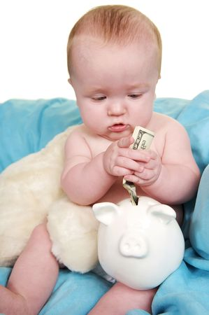 Up Close of cute baby putting money in a piggy bank Stock Photo