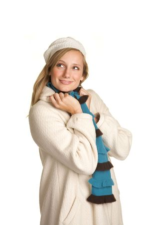 Pretty Blond wearing a winter white coat and hat with a bright scarf