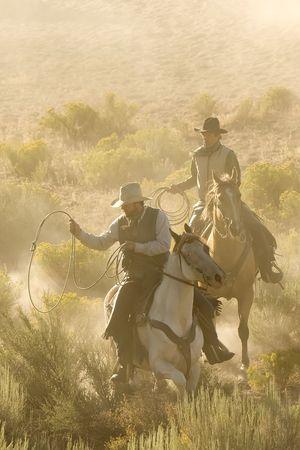 rowdy: Dos vaqueros galopante y cuerda a trav�s del desierto Foto de archivo