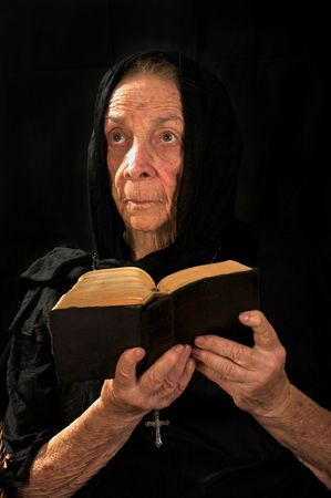 Old Catholic nun in prayer holding bible and rosary Stock Photo