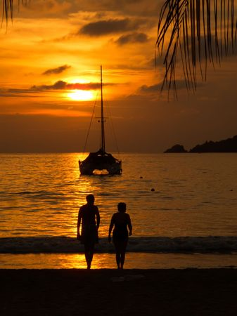 Sunset with sailboat and couple sihouetted in Zihuatanejo, Mexico