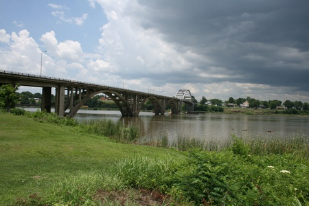 Bridge over a river with storm clouds in background and grass in foreground